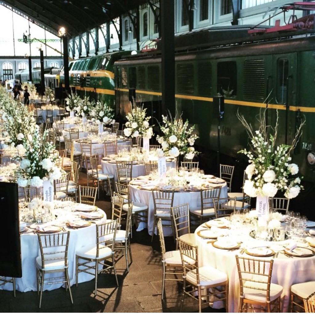 Preciosas mesa con grandes centros de flores en lso pasillos del museo del ferrocaril